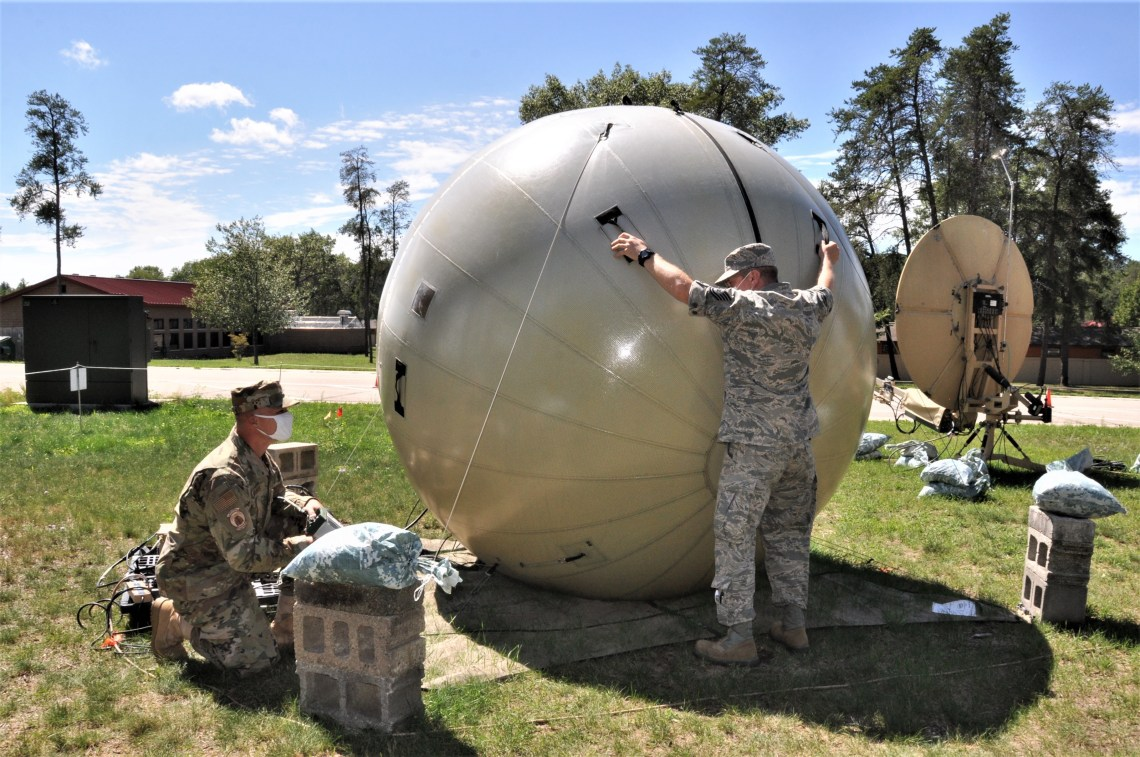 The radio frequency transmission specialists with the 271st Combat Communications Squadron, Pennsylvania Air National Guard, manually adjust a satellite system attached to a small-scale communications suite, in order to provide the strongest possible signal at the Alpena Combat Readiness Training Center.