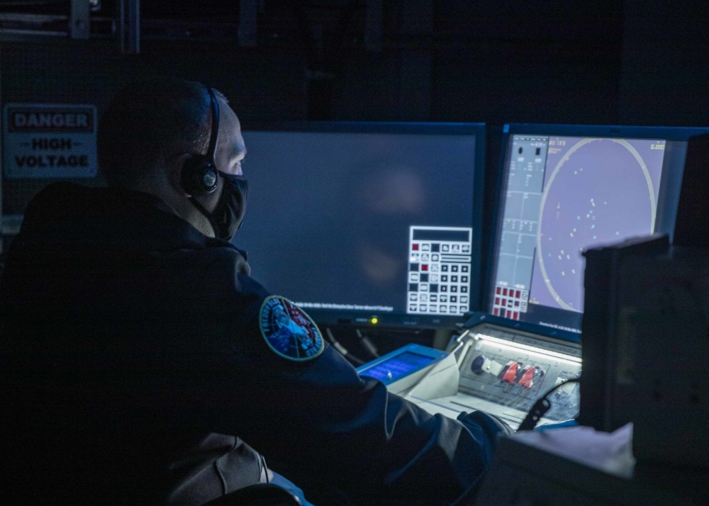 Operations Specialist 1st Class David Geary, from Davenport, Iowa, an air intercept controller, assigned to USS Gerald R. Ford's (CVN 78) operations department, stands watch at a console inside the ships Combat Direction Center July 30, 2020 during an Aircraft Intercept Control exercise