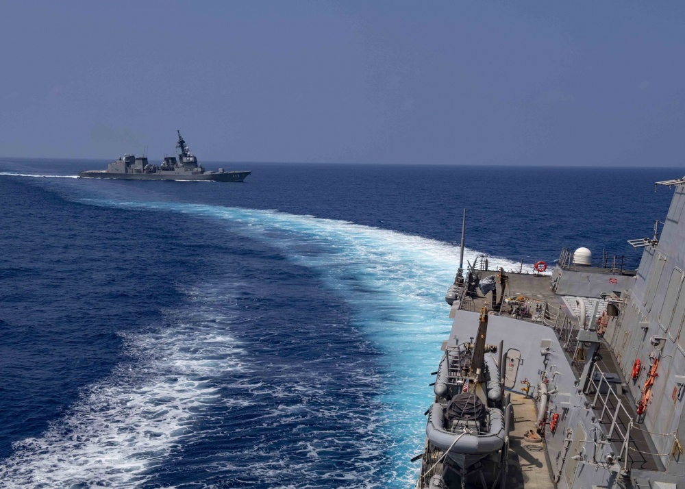 The Arleigh Burke-class guided-missile destroyer USS Mustin (DDG 89) sails alongside the Japanese Maritime Self-Defense Force ship JS Suzutsuki (DD 117).