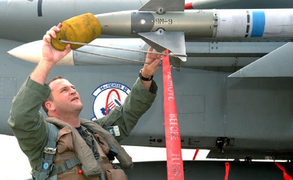 "AIM-9M Sidewinder with distinctive ""Dash-9"" lettering being preflighted by a USAF pilot. The blue stripe indicates that this example has an inert warhead intended for training purposes"