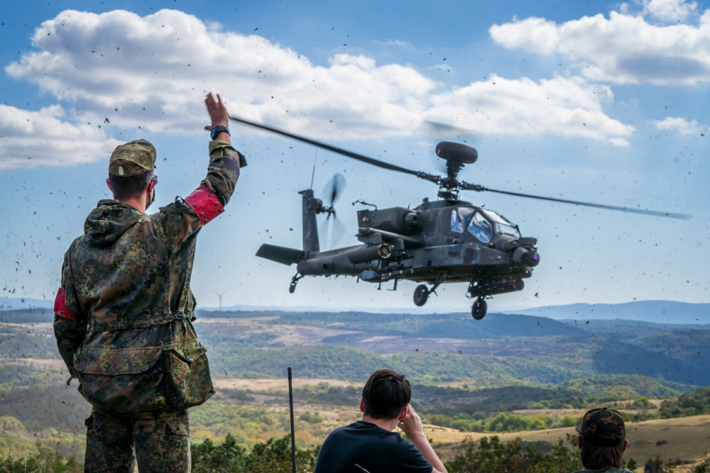 A Bundeswehr Soldier waves to an AH-64 Apache Longbow from A Co, 1-3 Attack Reconnaissance Battalion at Baumholder training area on Sep. 9.