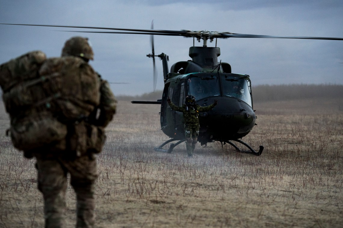 A Flight Engineer from a CH-146GriffonHelicopter directs members of the British Army 1st Battalion, The Rifles during Exercise MAPLE RESOVE.