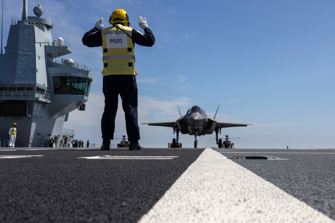 The Petty Officer of the Deck marshals the F-35 into position