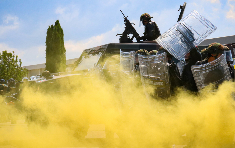 Italian Army Soldiers assigned to Regional Command-West, Kosovo Force, approach the main square through smoke during Operation Swift Rescue at the Gjakova/Gjakovë Airfield in Kosovo on June 10, 2021.