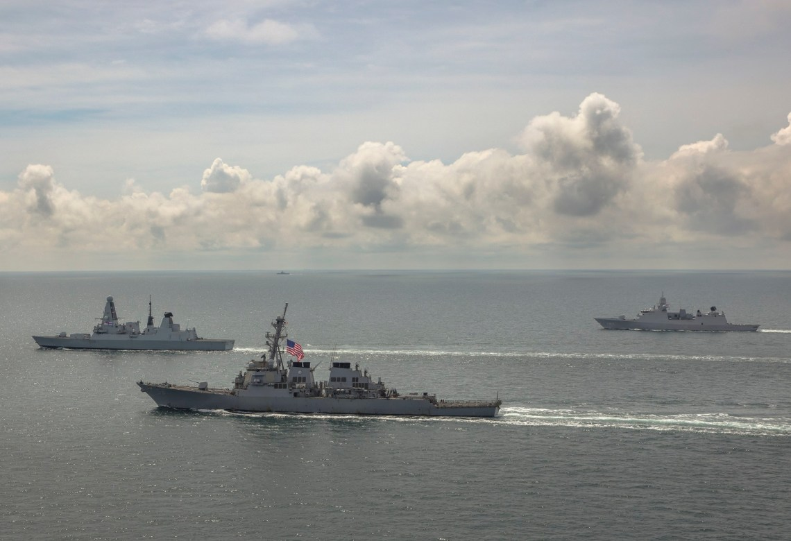 HMS Defender, USS Laboon and HMNLS Evertsen take station for close proximity sailing as a Russian warship watches from afar (rear of picture) whilst on maritime operations in the Black Sea.