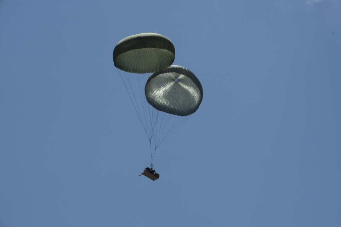 An Infantry Squad Vehicle (ISV) on a Dual Row Airdrop System (DRAS) airdrop descends above Holland Drop Zone at Fort Bragg, North Carolina under two G-11D cargo parachutes during operational testing.