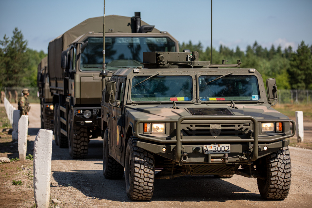 """Romanian Land Forces vehicles, the URO VAMTAC (front) and Iveco Military Truck (back) depart for deployment readiness exercise """"Rifle Ready"""" at Bemowo Piskie Training Area, Poland, July 1, 2021."""