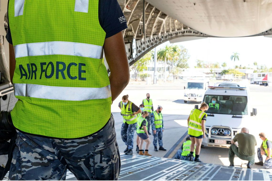 Australian Airforce ground crew assess the clearance of a St Johns Ambulance awaiting loading onto a C-17A Globemaster at RAAF Base Darwin, NT.