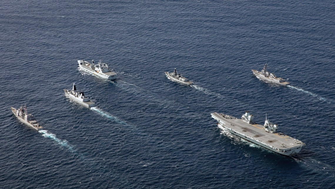 HMS Queen Elizabeth in formation with her Carrier Strike Group. The Carrier Strike Group comprises RFA Tideforce in the lead with HMS Northumberland (her right), USS Truxtun (her far right), HMS Dragon (her left), USS Philippine Sea (her far left) with HMS Queen Elizabeth at the rear.