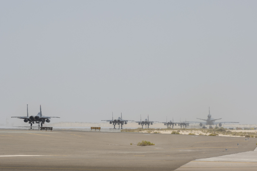 A KC-10 Extender from the 908th Expeditionary Air Refueling Squadron and several F-15E Strike Eagles assigned to the 494th Expeditionary Fighter Squadron prepare for takeoff July 5, 2021 from Al Dhafra Air Base, United Arab Emirates.