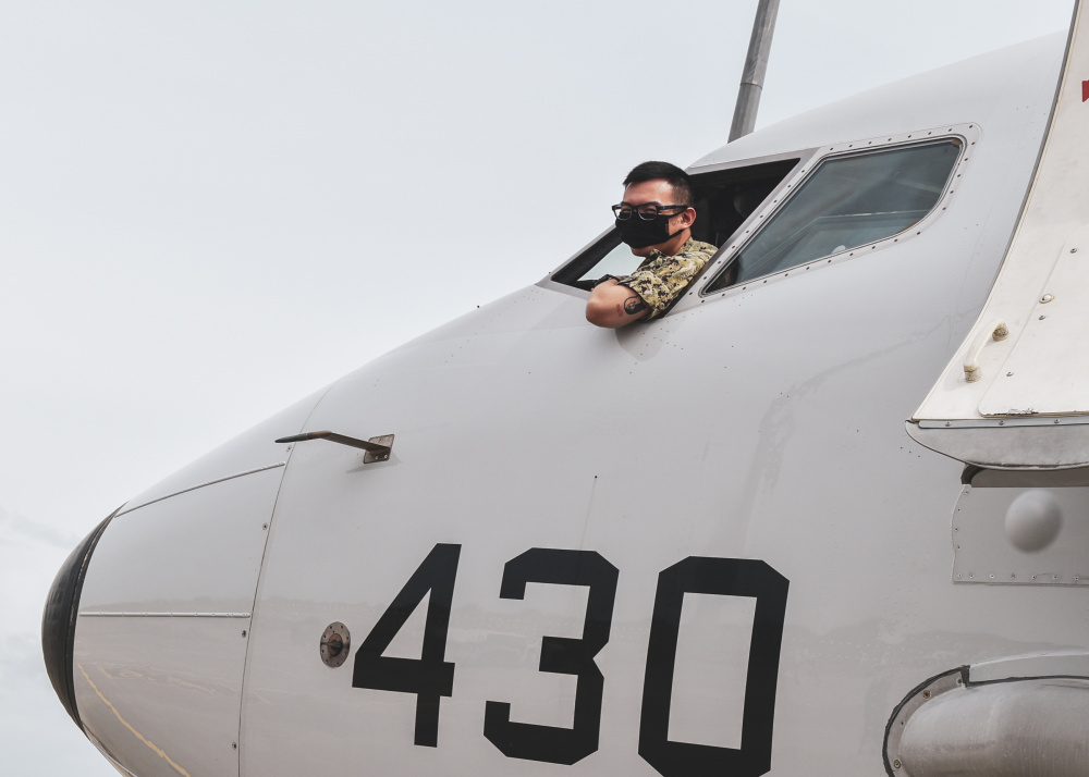 """Aviation Electronics Technician 2nd Class Jacky Xu, attached to the """"Red Lancers"""" of Patrol Squadron 10, conducts preflight checks on a P-8A Poseidon aircraft in support of a Cooperation Afloat Readiness and Training (CARAT) maritime exercise hosted by Sri Lanka."""