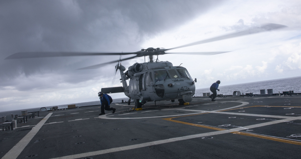 Sailors attach chocks and chains to an MH-60S Sea Hawk helicopter assigned to Helicopter Sea Combat Squadron (HSC) 28 Detachment Five during flight quarters aboard the Freedom-variant littoral combat ship USS Billings (LCS 15).