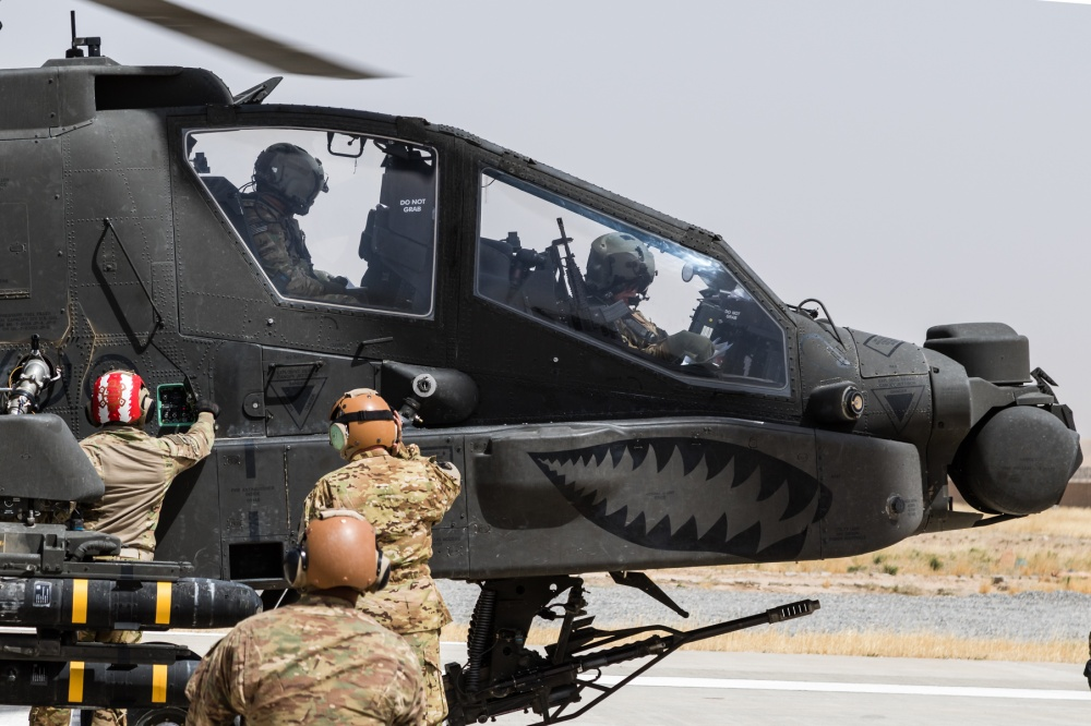 Petroleum Supply Specialists work together to refuel  an AH-64E Apache attack helicopter.