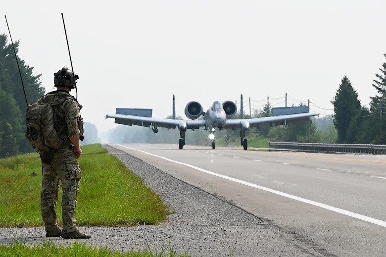 A special tactics operator from the 24th Special Operations Wing guides an A-10 Thunderbolt II from the Michigan Air National Guard's 127th Wing as it lands on a closed public highway Aug. 5, 2021 at Alpena, Mich., as part of a training exercise during Northern Strike 21.