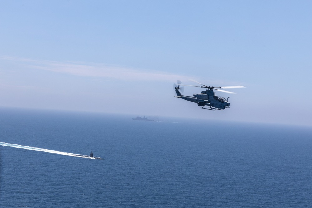 An AH-1Z Viper with Marine Light Attack Helicopter Squadron 267, Marine Aircraft Group 39, 3rd Marine Aircraft Wing (MAW), flies past a U.S. Navy Destroyer and Submarine during the Advanced Naval Basing evolution of Summer Fury 21 at San Clemente, California, July 20, 2021.