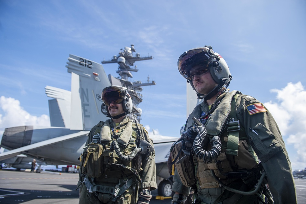 Pilots assigned to the Bounty Hunters of Strike Fighter Squadron (VFA) 2 prepare to enter an F/A-18F Super Hornet from the flight deck of Nimitz-class aircraft carrier USS Carl Vinson (CVN 70), Aug. 26, 2021.