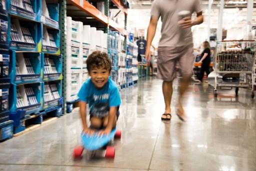 boy riding skateboard through store