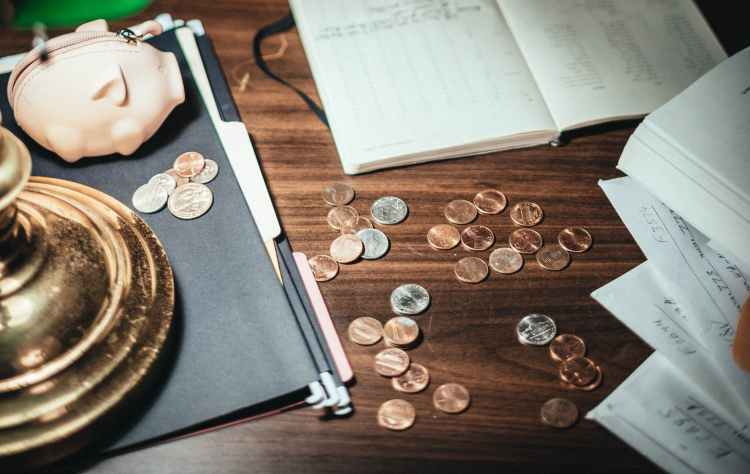 coins scattered on desk with papers and creative pig wallet
