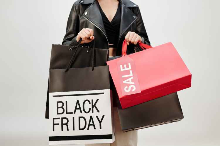 woman in black leather jacket holding red and white box