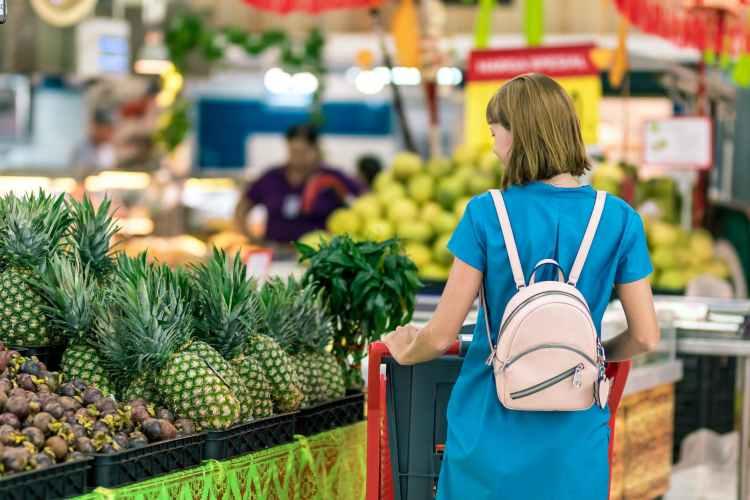 woman standing beside pineapple fruits