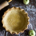 buttery flaky pie dough blind baked, resting on a countertop besides two green apples and a wooden rolling pin.