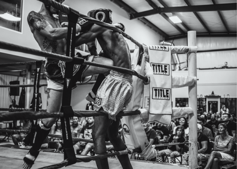 two male muay thai fighters fighting with crowd