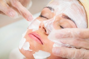 Beautiful woman with facial mask at beauty salon. Pretty woman receiving facial massage. Spa therapy for young woman receiving facial mask at beauty salon - indoors