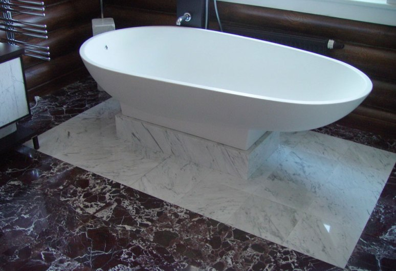 Ванна на мраморном подиуме в интерьере ванной комнаты