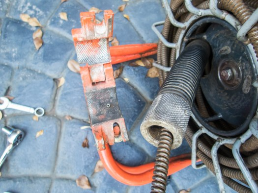 If you have to open the clamp to fix a tangle or realign the drain cleaner's feed tube, be aware of the little pin.