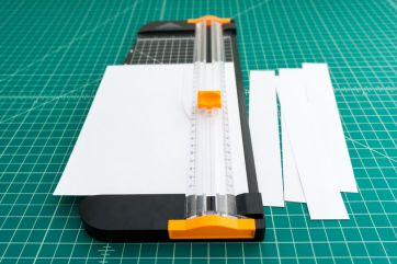Cutting the paper strips for the compact gloves for first aid kits or auto work