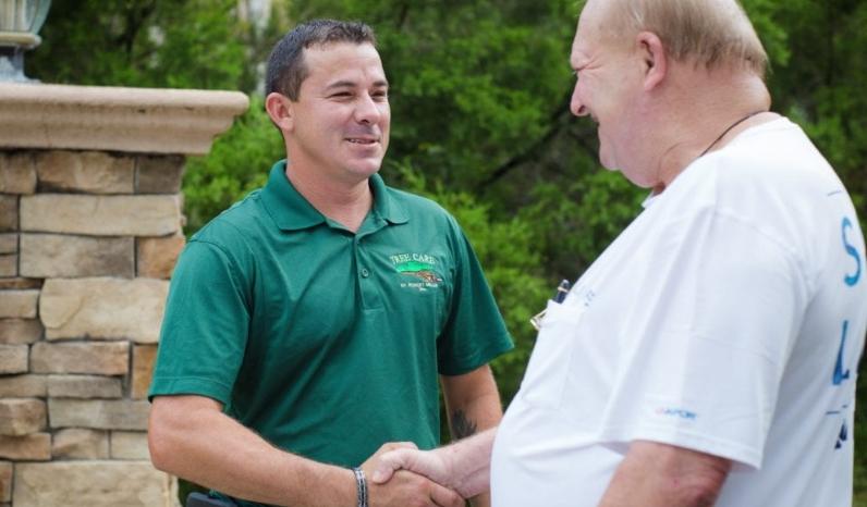 Foreman, Jeff, shakes hand with happy customer after tree work