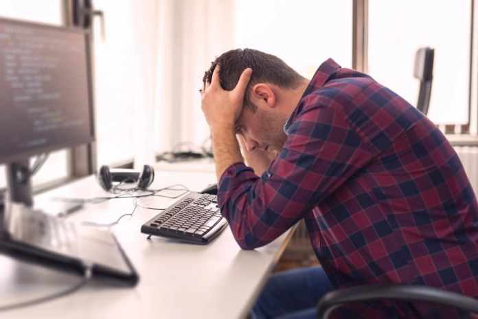 Man sitting at desk, worn out from work