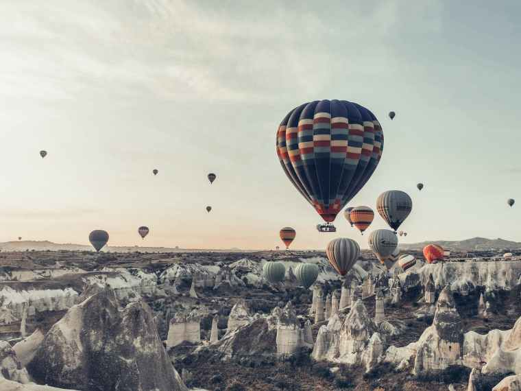 colorful air balloons flying over picturesque rocky terrain