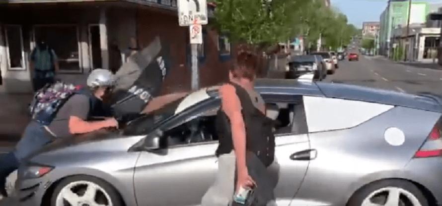 Protester Jumps On Car, Driver Slowly Keeps Driving, Leftists Blame Driver