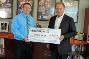 Joseph Lacey (left) poses for a photo with Michigan State University basketball coach Tom Izzo after accepting his Excellence in Education Award from the Michigan Lottery.