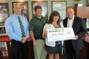 Kristen Bickel (second from right) poses for a photo with Woodside Elementary principal, Nick Holtvluwer  (left), her husband, Doug Bickel (second from left) and Michigan State University basketball coach Tom Izzo after accepting her Excellence in Education Award from the Michigan Lottery.