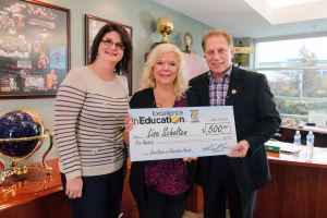 Lisa Scholten (center) poses for a photo with Beagle Elementary School principal, Dawn Kennaugh (left), and Michigan State University basketball coach Tom Izzo after accepting her Excellence in Education Award from the Michigan Lottery.