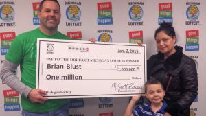 Brian Blust poses for a photo with his wife, Margie, and son after collecting his $1 million Powerball prize.
