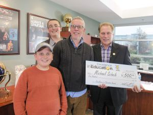 Michael Scheib (center) poses for a photo with his sons (left to right) Alden and Ethan, and Michigan State University basketball coach Tom Izzo after accepting his Excellence in Education Award from the Michigan Lottery.