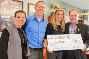 Amy Watts (second from right) poses for a photo with her mother, Nancy Chapman, Livonia teacher, Christopher Pinta, and Michigan State University basketball coach Tom Izzo after accepting her Excellence in Education Award from the Michigan Lottery.