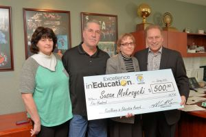 Susan Mokrzycki (second from right) poses for a photo with (left to right) sister-in-law, Barb Mokrzycki, brother, Ken Mokrzycki, and Michigan State University basketball coach, Tom Izzo, after accepting her Excellence in Education Award from the Michigan Lottery.