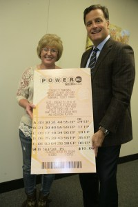 Julie Leach, of Three Rivers, holds an enlarged copy of her winning Powerball ticket while posing for a photo with Michigan Lottery Commissioner, M. Scott Bowen.