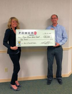 Sarah Suchyta, key account specialist for the Michigan Lottery, presents Mike LaBerteaux, merchandising manager for Walters-Dimmick Petroleum, with an oversized check for $50,000, which represents the bonus commission the company received for selling the jackpot-winning ticket.