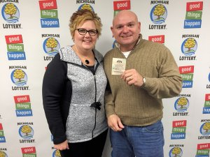 Robert Carmona and his wife, Becky, pose for a photo after collecting his $25,000 a year for life prize.