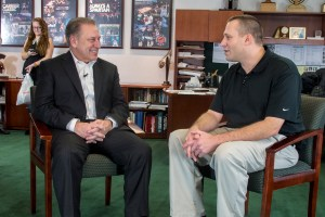 Daniel Carr talks with Michigan State University basketball coach, Tom Izzo, after accepting his Excellence in Education award.