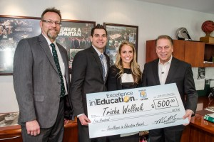 Trisha Wellock poses for a photo with her husband, Andrew, and colleague, Tom Timmer (far left), after accepting her Excellence in Education award from Michigan State University basketball coach Tom Izzo.