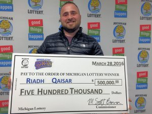 Riadh Qaisar smiles after claiming his $500,000 prize from the Michigan Lottery.