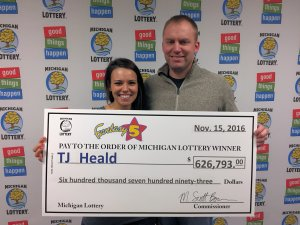 TJ Heald and his wife, Sarah, smile after collecting a Fantasy 5 jackpot.