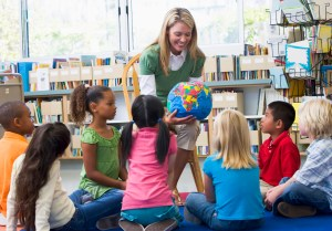 Kindergarten teacher and children looking at globe
