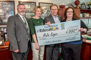 Malia Koger poses for a photo with Olivet High School principal, Troy Waffle, and friend and colleague, Lisa Weaver, after accepting her Excellence in Education award from Michigan State University basketball coach Tom Izzo.